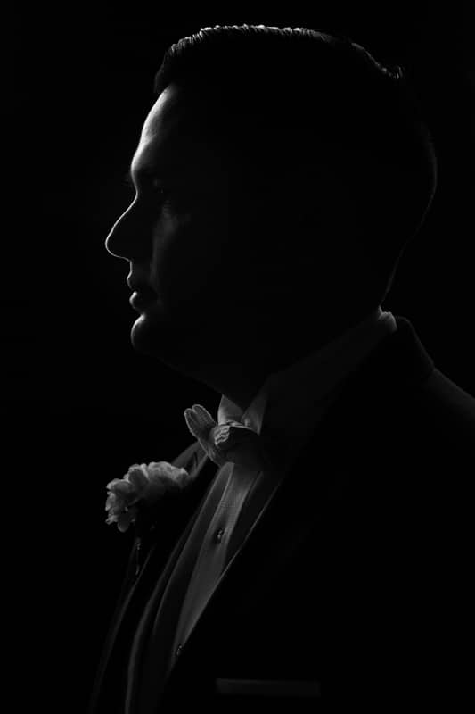 a dramatic black and white Fuji 16-55mm portrait shot of a groom