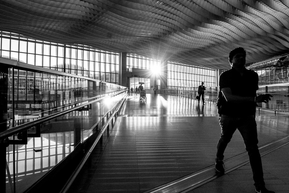 Man walking down an airport aisle in hong kong
