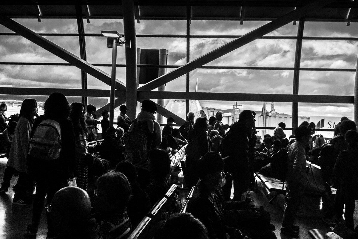A crowd of people looking at the right in an airport
