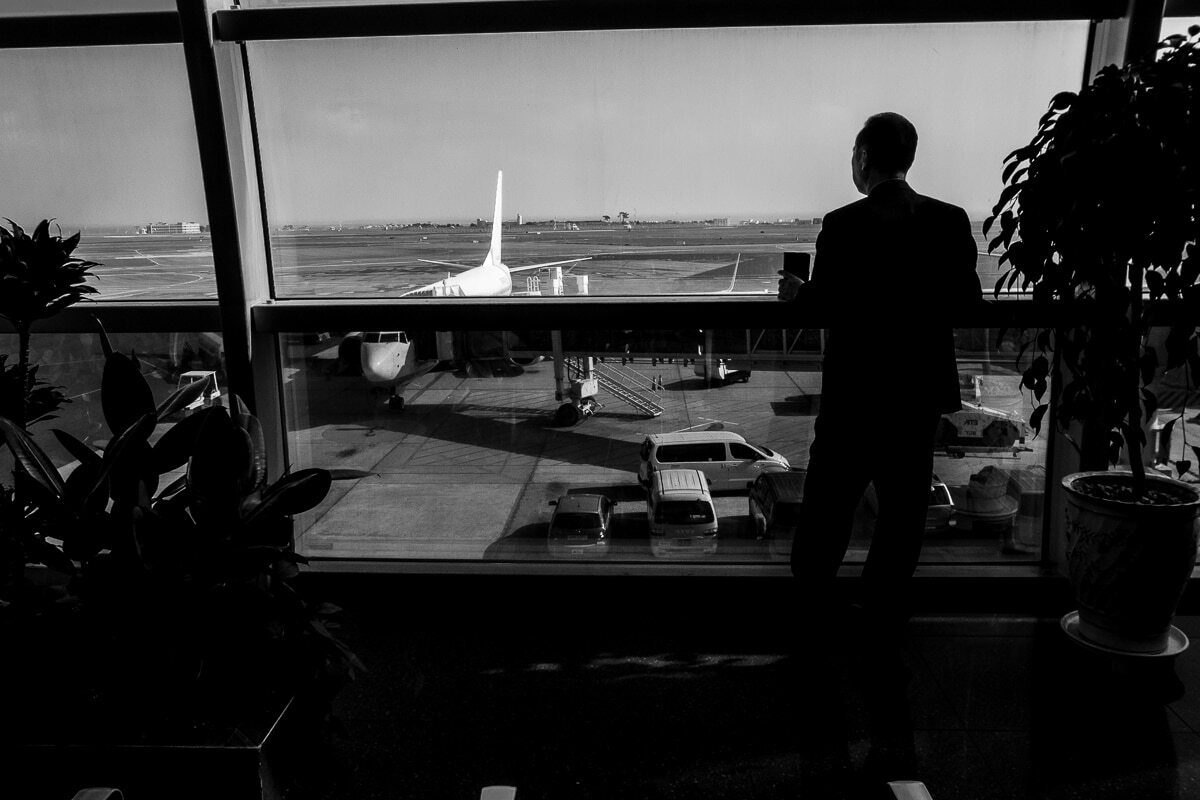 Man looking out the window of an airport